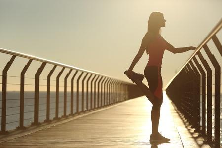 Girl stood on bridge stretching before run.jpg