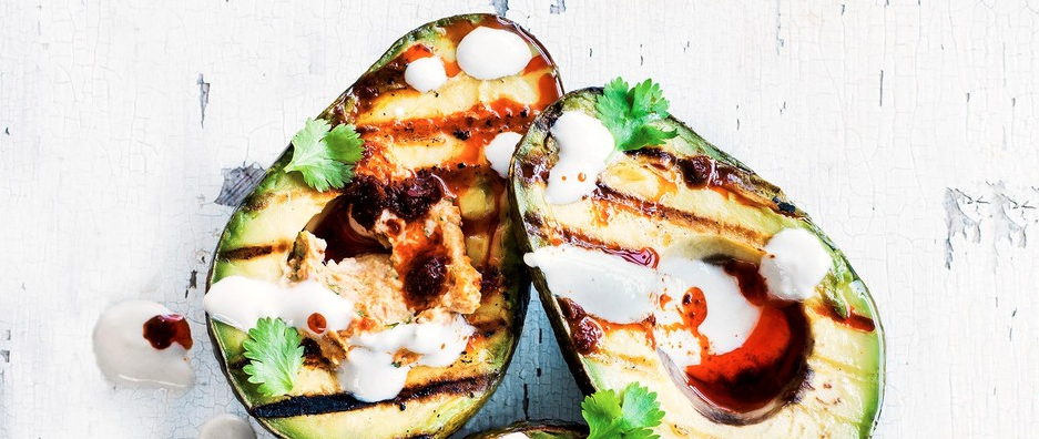 Grilled avocado halves with harissa hummus and tahini yogurt