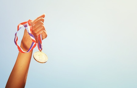 Outstretched-arm-holding-a-medal.jpg